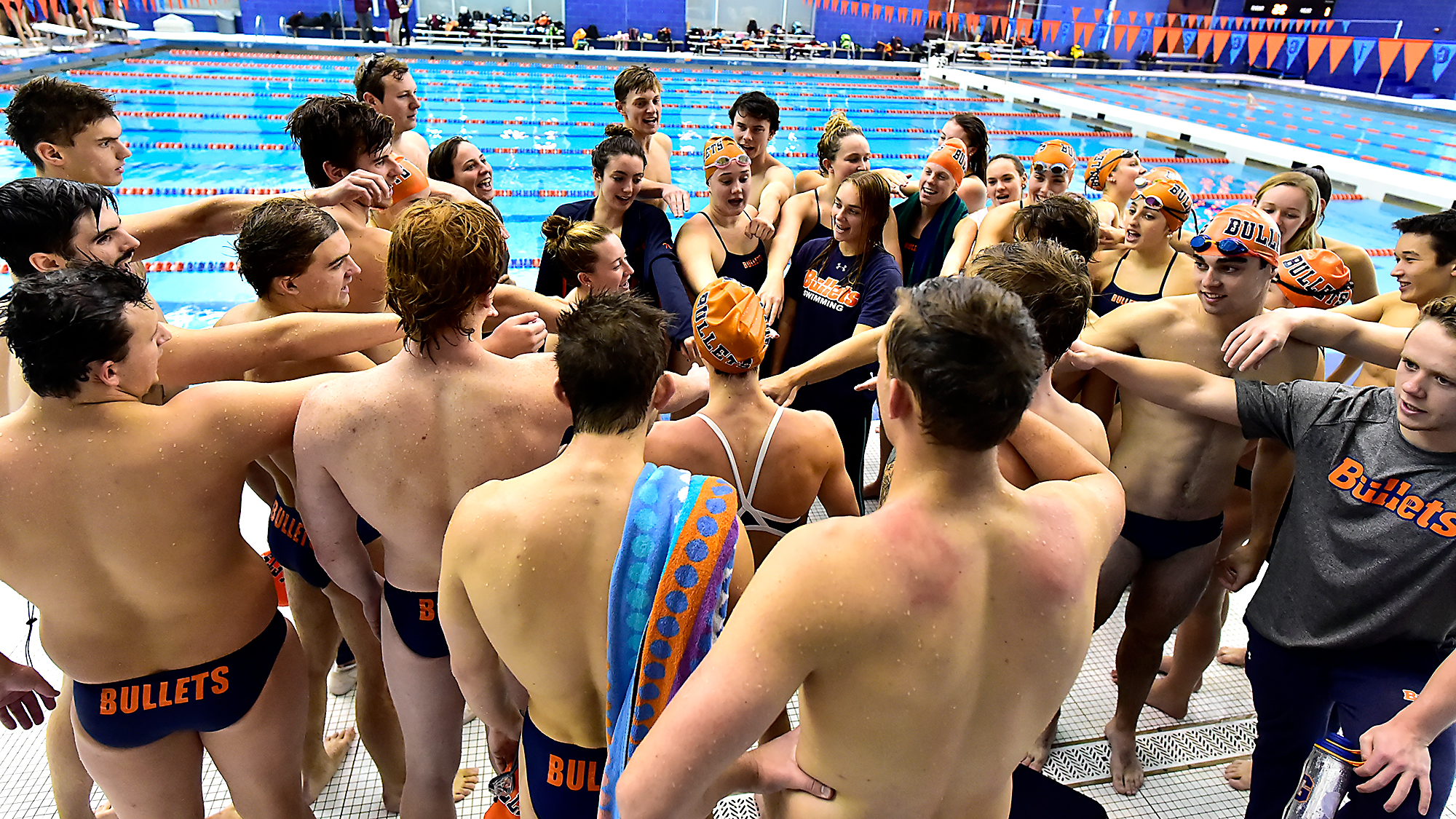 The Bullets swim teams huddle together on the pool deck.
